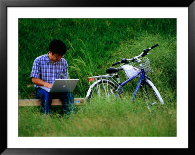 Man Using Laptop Computer Beside His Bicycle Near Kamogawa River, Kyoto, Japan by Frank Carter Pricing Limited Edition Print image