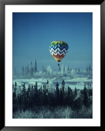 Hot Air Balloon Hovers Over A Snowy Landscape by George Herben Pricing Limited Edition Print image