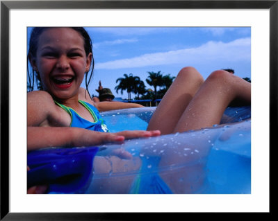 Young Girl Floating In Swimming Pool In Rubber Ring, Gold Coast, Australia by Richard I'anson Pricing Limited Edition Print image