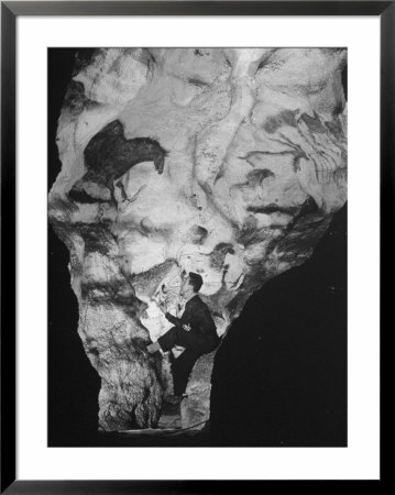 Man Looking At Prehistoric Cave Painting by Ralph Morse Pricing Limited Edition Print image