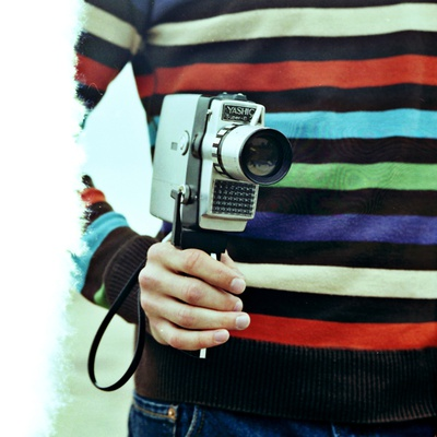 A Young Man Holding An Old Cine Camera by Jewgeni Roppel Pricing Limited Edition Print image