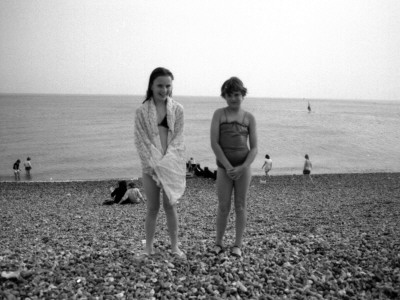 Two Little Girls Pose For Their Photo On A Pebbly Brighton Beach by Vanessa Wagstaff Pricing Limited Edition Print image